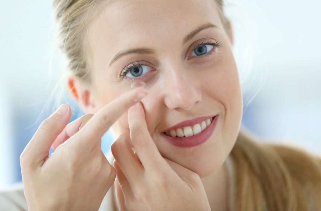 Happy young lady putting contact lens into her right eye