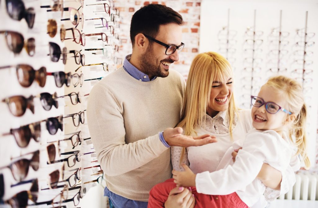 Family at optometrist office helping daughter choose a pair of glasses