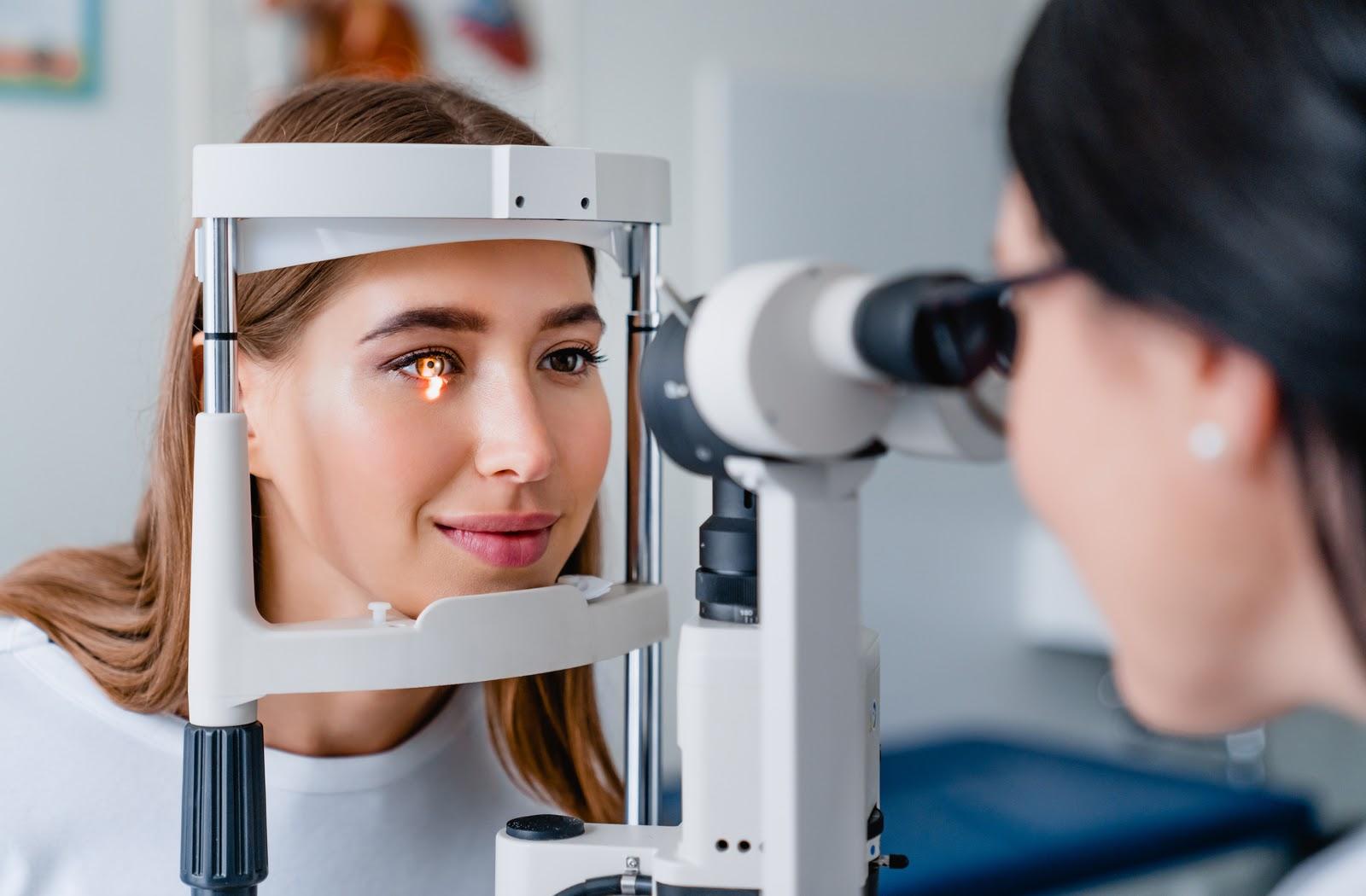 Young women undergoing eye exam by her optometrist