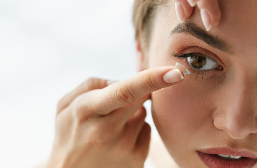 Women putting on contact lenses while looking ahead